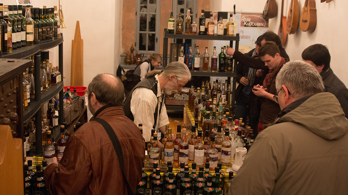 Blick auf einen Messe-Stand mit mehreren Gästen und vielen Whisky-Flaschen