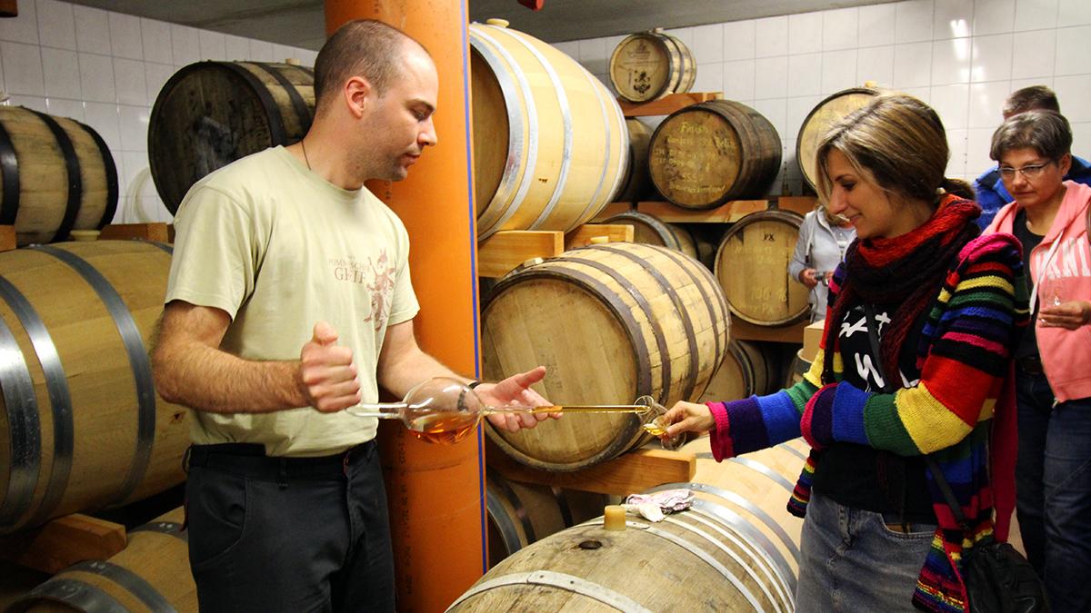 Der Brennmeister bei der Verkostung in der Hofbrennerei füllt gerade Whisky aus einem Madeira-Fass in ein Nosing-Glas eines Gastes