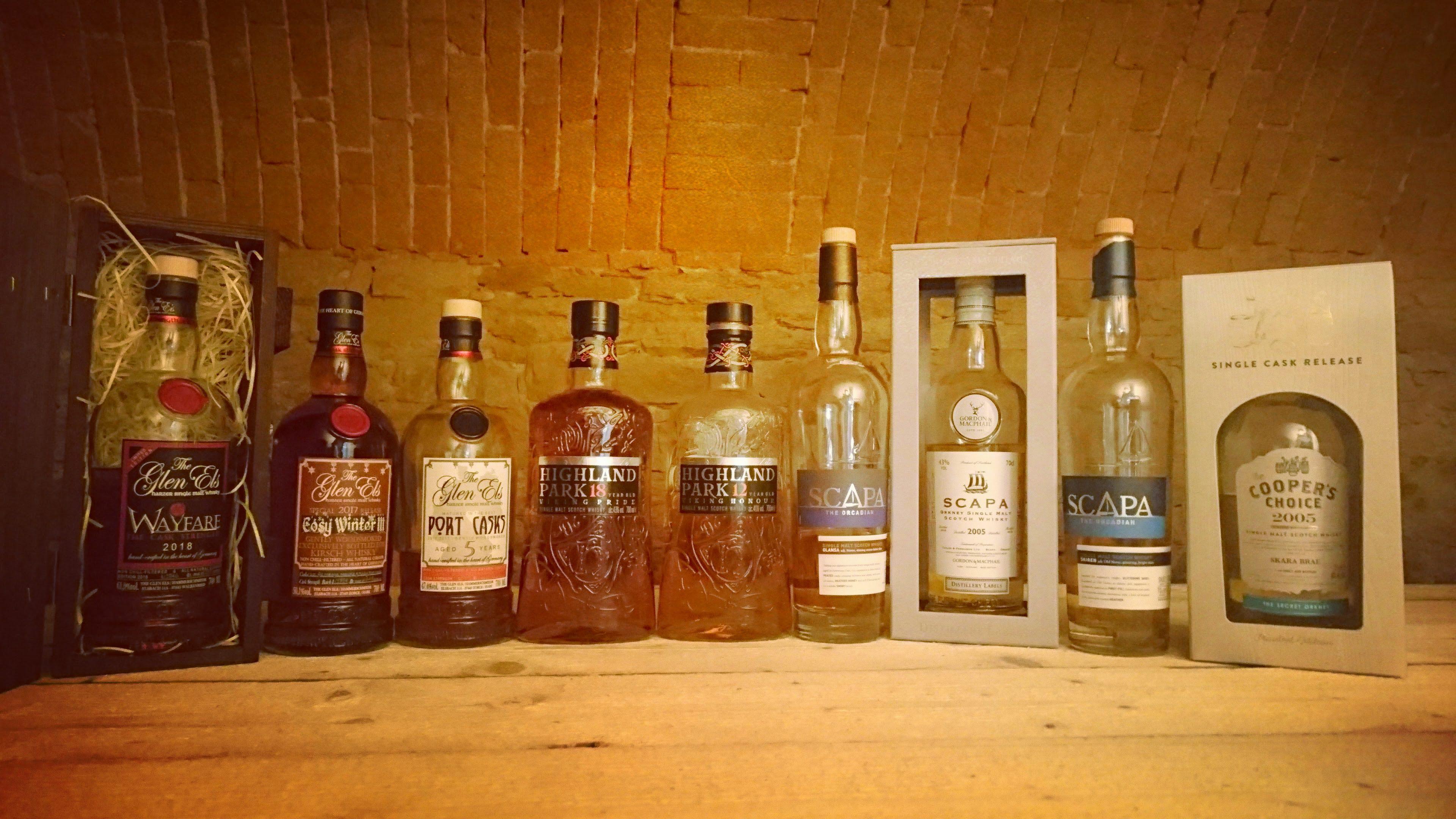 Neun verschiedene Whisky-Flaschen nebeneinander auf dem neuen Tisch im Gewölbekeller angeordnet