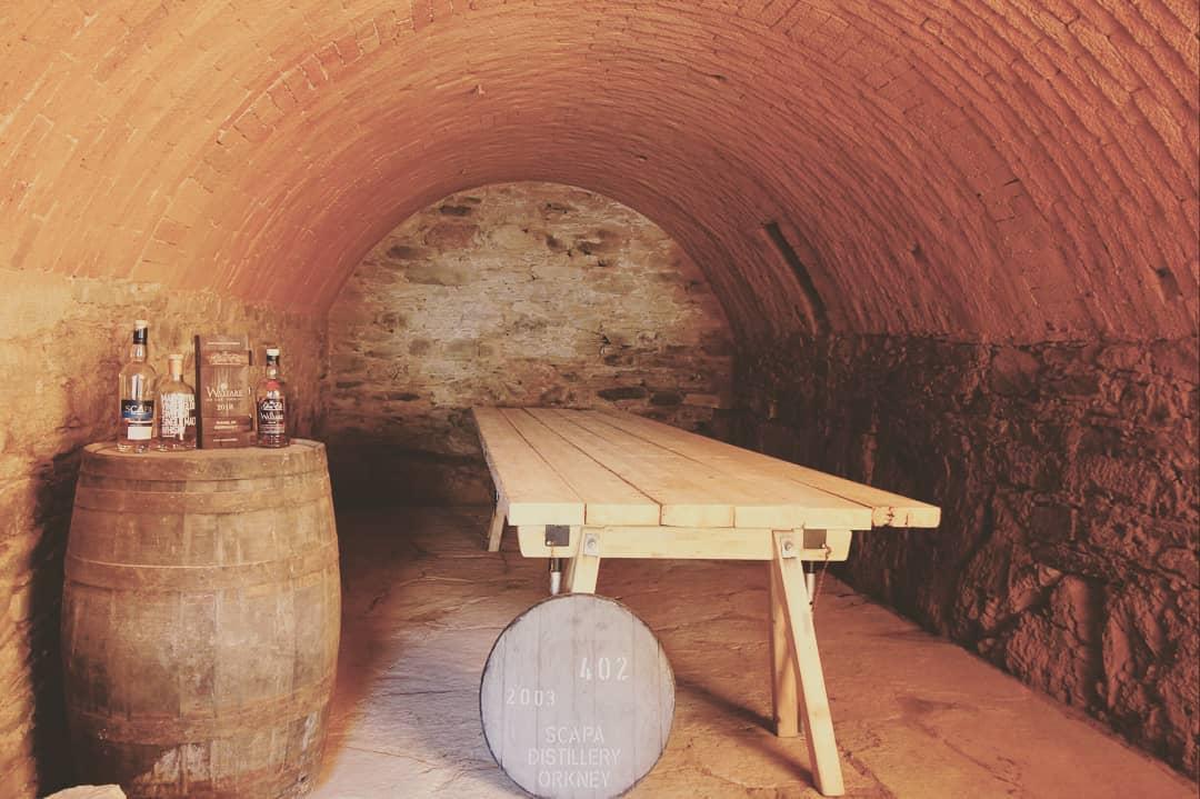 Blick in den Gewölbe-Keller mit dem neuen Tisch in der Mitte und dem Whisky-Faß links.