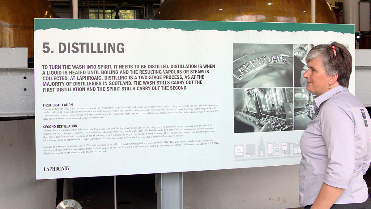 Eine Frau steht vor einer Info-Tafel mit einem Erklärungstext zum Distilling