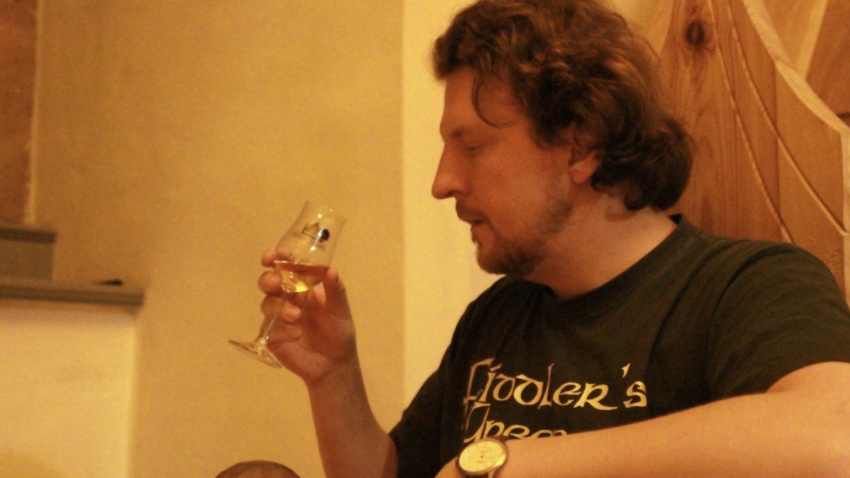Ein Mann hält ein Nosing-Glas mit Whisky in seiner Hand